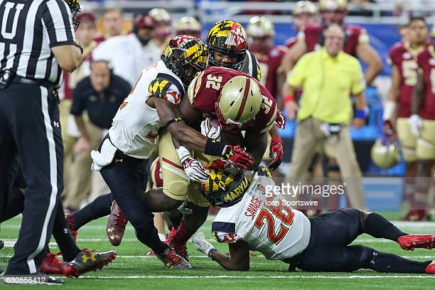 Boston College Eagles running back Jon Hilliman is tackled by Maryland Terrapins defensive back Darnell Savage Jr during Quick Lane Bowl game action...
