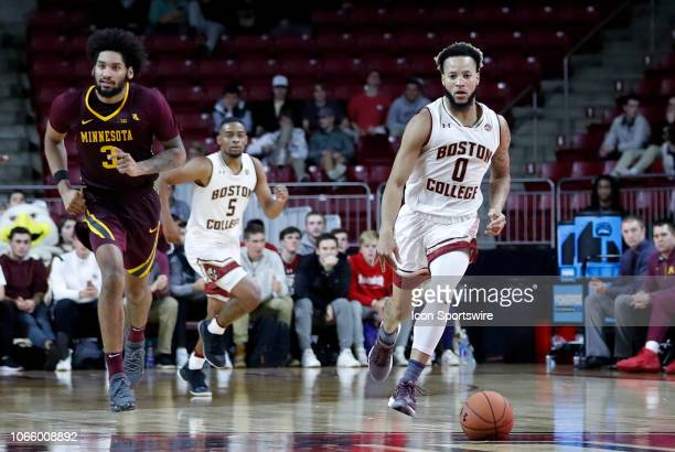 Boston College guard Ky Bowman pushes the ball up court as Minnesota Golden Gophers forward Jordan Murphy looks for cover during a game between the...