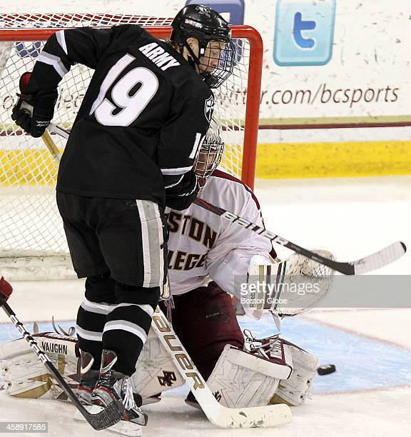 Boston College men's ice hockey goalie Parker Milner makes a save as Providence College's Derek Army, tries for the tip in.