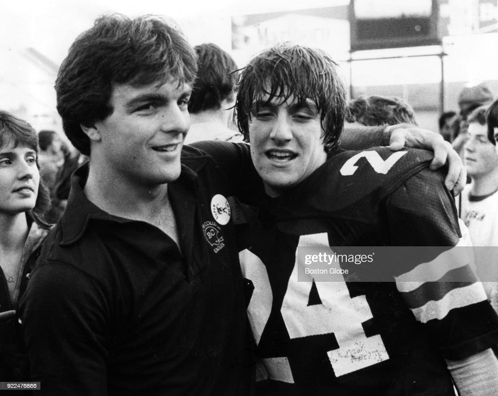 Boston College quarterback Doug Flutie, left, and his brother Darren Flutie, right, pose for a photo after Darren scored a winning touchdown for Natick during a division one game against Melrose, Dec. 4, 1982.