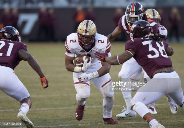 Boston College running back AJ Dillon rushes upfield attempting to elude Virginia Tech safety Reggie Floyd and linebacker Rico Kearney during a game...