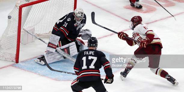 Boston College's JD Dudek puts the puck past Northeastern goalie Cayden Primeau in the third period to pull Boston College within one goal trailing...
