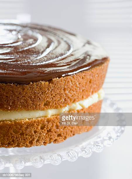 Boston cream pie on glass cake stand, elevated view, close up