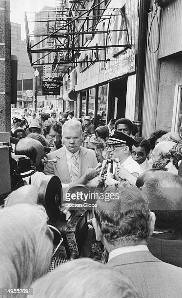 Boston Deputy Supt. John Barry, in plainclothes, listens as Boston Detective Lt. Jerome McCallum speaks to reporters at a press conference outside...