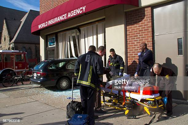 Boston EMTs tend the victim of a car crash after her car went through window of World Insurance Agency after being hit by a pickup truck at the...