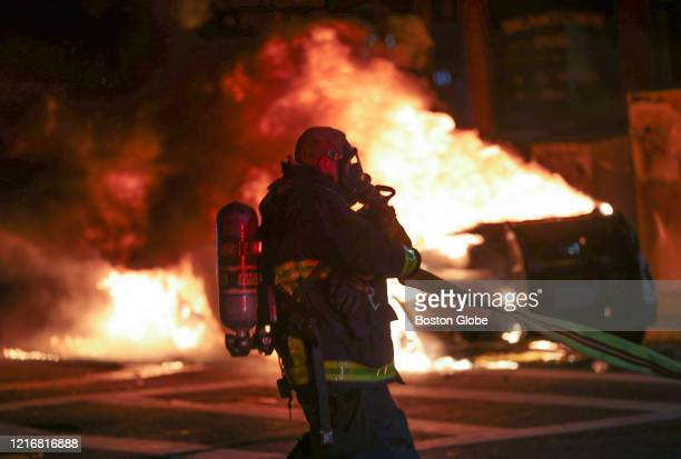 Boston Firefighters puts on a dry hose about to put out a fire of a Boston Police car on Tremont Street in Boston after tensions rose following a...