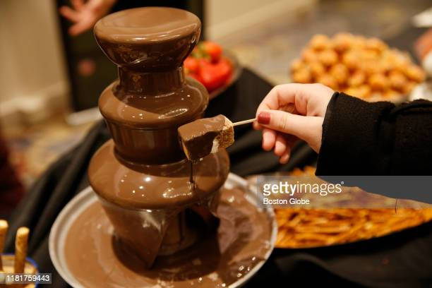 Boston Globe reporter Felicia Gans dips into the CBD chocolate fountain by Southern Maine Kitchen at the Cannabis Wedding Expo in Cambridge MA on Nov...
