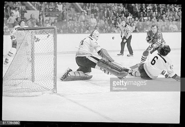 Goalie Jacques Plante playing his first game for the Boston Bruins turns away shot by Black Hawks' Ralph Backstrom while Bruins' Nick Beverly falls...