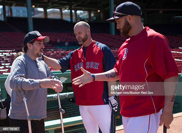 Boston Marathon bombing Jeff Bauman is greeted by David Ross and Jonny Gomes of the Boston Red Sox before throwing a batting practice session before...