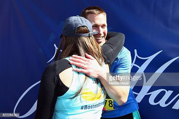 Boston Marathon bombing survivors Patrick Downes and Jessica Kensky celebrate at the finish line with their dog Rescue after Downes completed the...