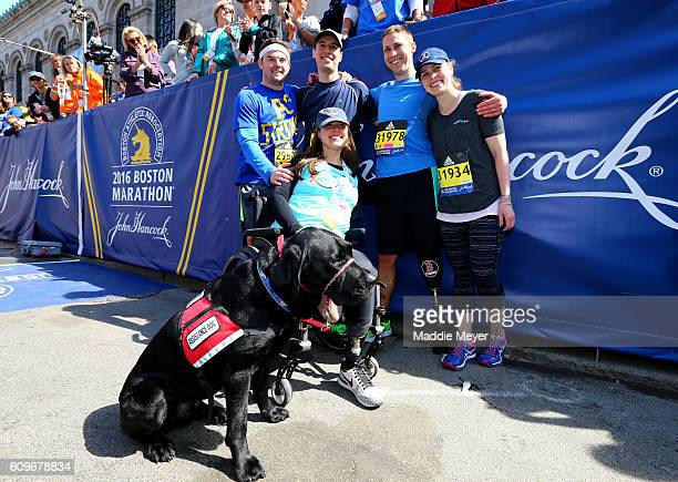 Boston Marathon bombing survivors Patrick Downes and Jessica Kensky celebrate at the finish line with their dog Rescue and fellow runners after...