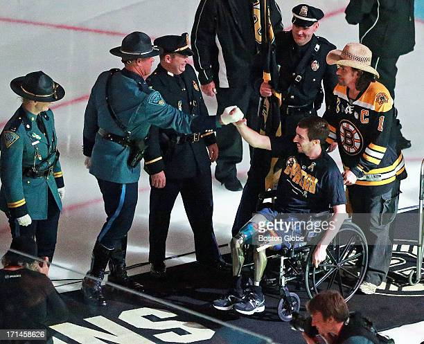 Boston Marathon bombing victim Jeff Bauman and Carlos Arredondo are greeted by the police officers as they leave the ice following the pregame flag...