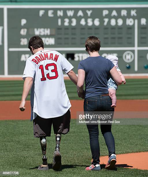Boston Marathon bombing victim Jeff Bauman heads to the mound with his wife Erin Hurley to throw out a ceremonial first pitch before a game between...