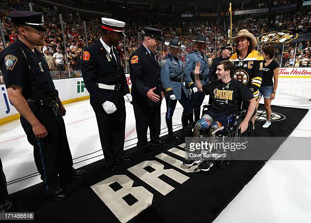 Boston Marathon bombing victim, Jeff Bauman, high fives service men and women while pushed by Carlos Arredondo, the man who came to his aid...