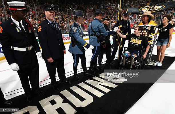 Boston Marathon bombing victim Jeff Bauman high fives service men and women while pushed by Carlos Arredondo the man who came to his aid immediately...