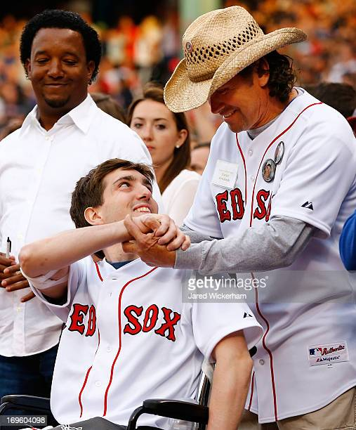 Boston Marathon bombing victim, Jeff Bauman, holds the hand of Carlos Arredondo, the man who came to his aid immediately following the explosions,...
