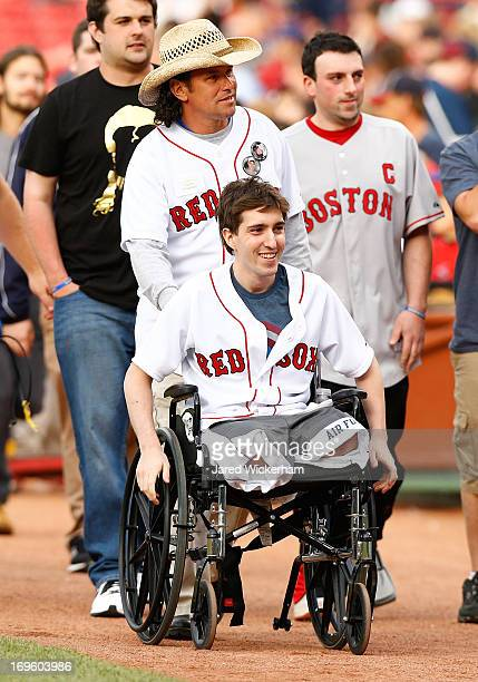 Boston Marathon bombing victim, Jeff Bauman, is wheeled out to the pitchers mound before throwing out the ceremonial first pitch by Carlos Arredondo,...