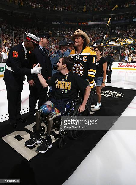 Boston Marathon bombing victim Jeff Bauman shakes hands with service men and women while pushed by Carlos Arredondo the man who came to his aid...