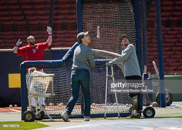 Boston Marathon bombing victims Patrick Downes left and Jeff Bauman track a fly ball hit by Jonny Gomes of the Boston Red Sox during a batting...