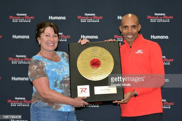 Boston Marathon Champion Meb Keflezighi presents a Hall of Fame recipient Sherry Ricker with an award at the Health Fitness Expo during Humana Rock...