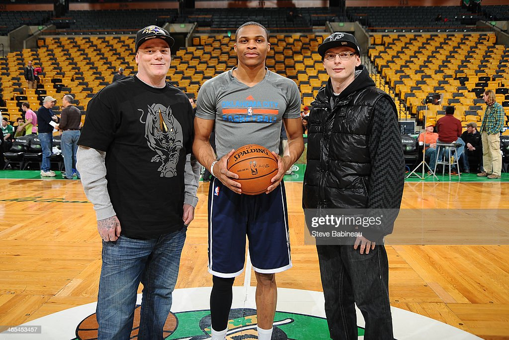 Boston Marathon survivor, Paul Nordren and friend, pose at center court with Russell Westbrook #0 of the Oklahoma City Thunder before the game against the Boston Celtics on January 24, 2014 at the TD Garden in Boston, Massachusetts.