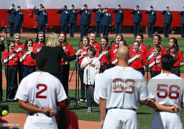 Boston Marathon victim Jane Richard and members of the St Ann's Children's Choir of Dorchester sing the national anthem before the game The Boston...