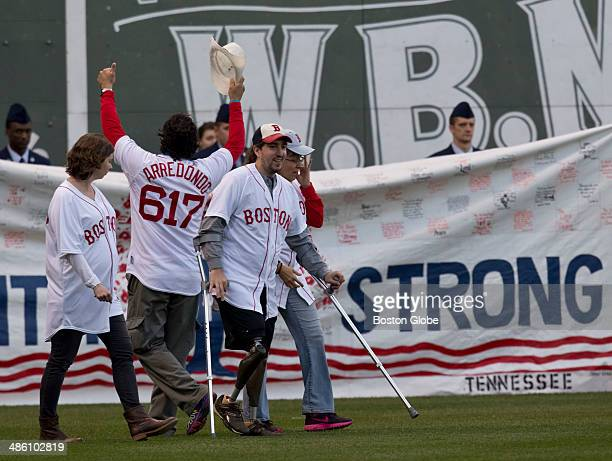 Boston Marthon bombing survivor Jeff Bauman right Carlos Arredondo who saved his life arms up and Erin Hurley Bauman's fiancee left walk onto the...