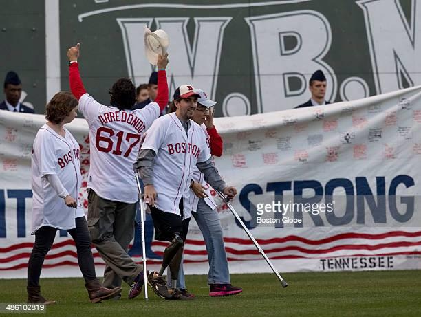 Boston Marthon bombing survivor Jeff Bauman, right, Carlos Arredondo, who saved his life, arms up, and Erin Hurley, Bauman's fiancee, left, walk onto...