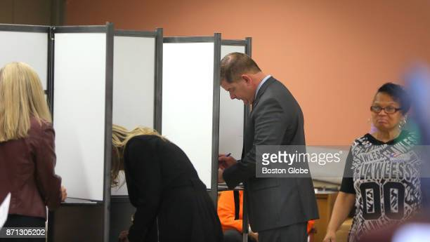 Boston Mayor Martin J Walsh votes with his partner Lorrie Higgins left and her daughter Lauren Campbell center at the Lower Mills Branch of the...