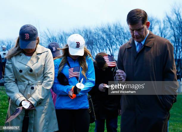 Boston mayor Marty Walsh and his family bow their heads during a moment of silence at a candlelight vigil for the oneyear anniversary of the Boston...