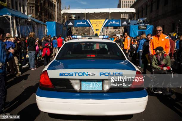 Boston police car drives through crowds of people towards the finish line of the Boston Marathon on April 20 2014 in Boston Massachusetts This year's...