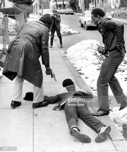 Boston Police Detective Charles Horsely, left, keeps a suspect at bay while his partner, Detective Paul Williams, reaches for handcuffs on Wayne...