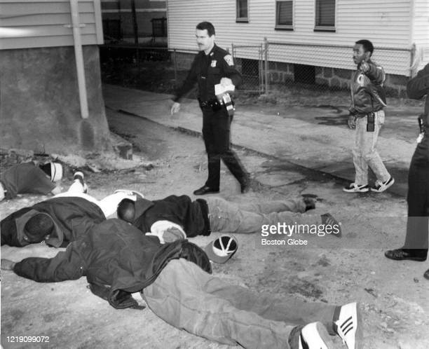 Boston Police Detective Trent Holland, right, orders a group of young men to keep face down on the ground as he and other officers chased the group...