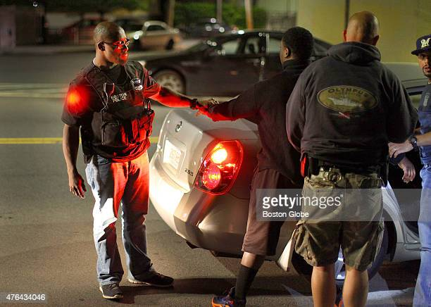 Boston Police gang unit officer Andrew Hunter holds onto the hand of a man that was pulled over on Talbot Avenue in Dorchester as he is patted down...