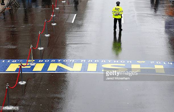 Boston Police officer stands guard at the finish line of the Boston Marathon prior to the flag raising ceremony commemorating the oneyear anniversary...