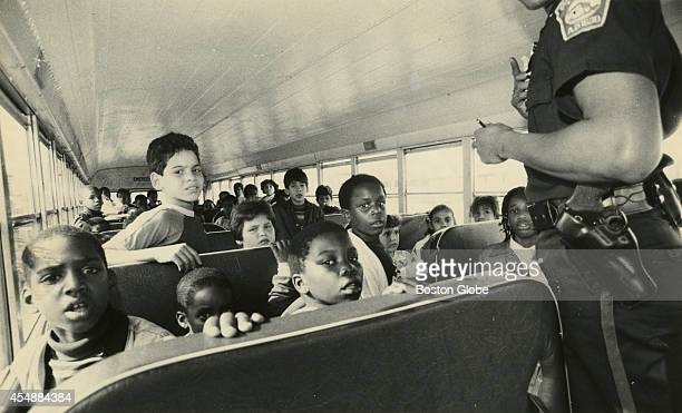 Boston police officer talks with students from Dorchester who were riding the school bus that was stoned at Preble Circle in South Boston on Sept 17...