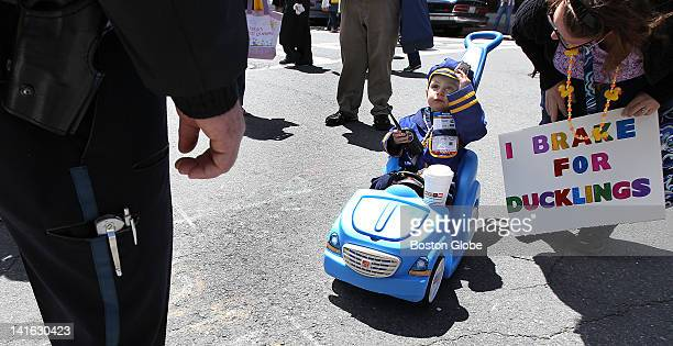 """Boston Police Officer William O'Hara is greeted at Charles and Chestnut streets by Mac Lamar, who is dressed as """"Officer Michael."""" The 2-year-old's..."""