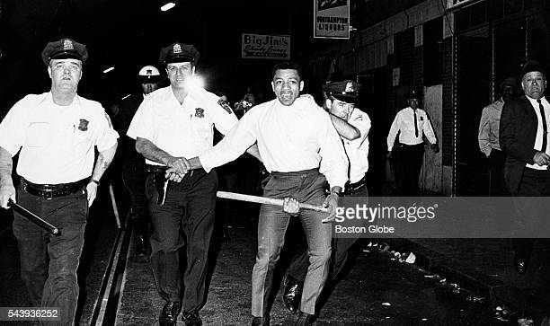 Boston Police officers carrying batons walk a man away from a riot at Washington and Northampton Streets in Roxbury on June 3 1967 Riots broke out...