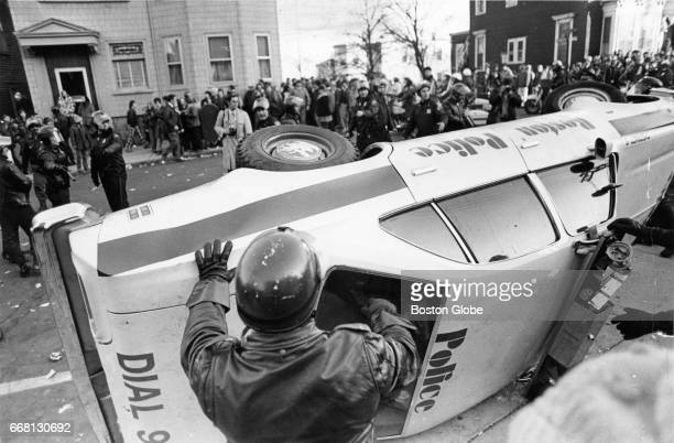 Boston Police officers flip a police cruiser back over after it was overturned by a crowd during a disturbance at South Boston High School on Dec 11...