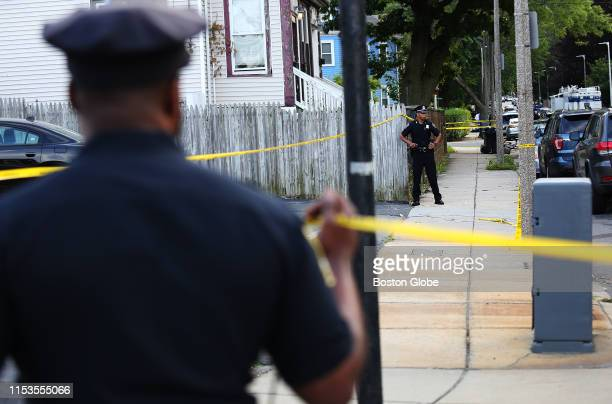 Boston Police officers stand at the scene of a police-involved shooting on Penhallow Street in the Dorchester neighborhood of Boston on June 24,...
