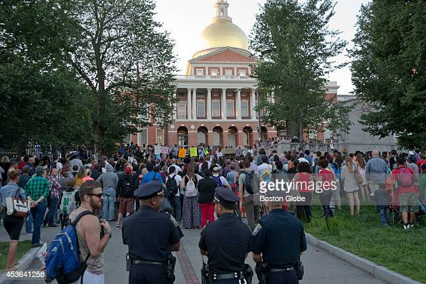 Boston Police officers stand watch during a rally on August 14, 2014 protesting the death of Michael Brown, who was fatally shot by the Ferguson, Mo....