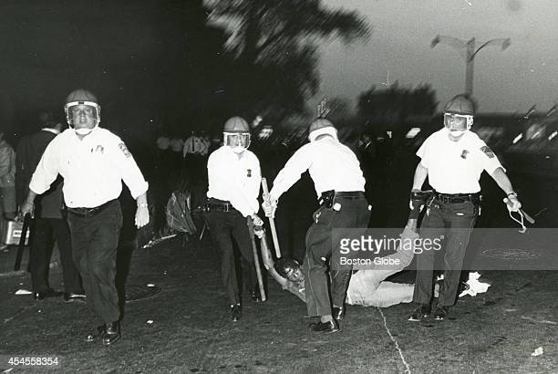 Boston Police officers wearing riot helmets and carrying batons arrest rioters in Roxbury on June 2, 1967. Riots broke out across the neighborhood in...