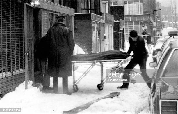 Boston Police remove the body of a shooting victim from a Chinatown social club in Boston on Jan. 12, 1991. Five men playing cards at the after-hours...