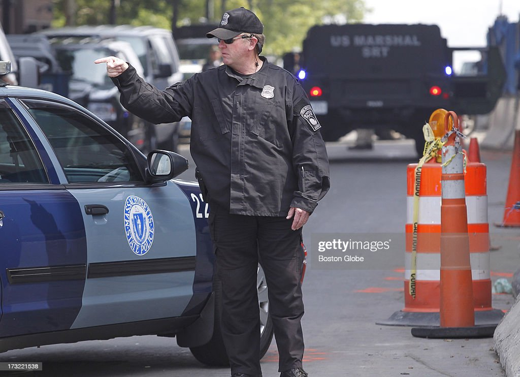 A Boston Police Special Operations officer gestures as a motorcade carrying alleged Boston Marathon bomber Dzhokhar Tsarnaev arrives at the John Joseph Moakley Courthouse in Boston, July 10, 2013.
