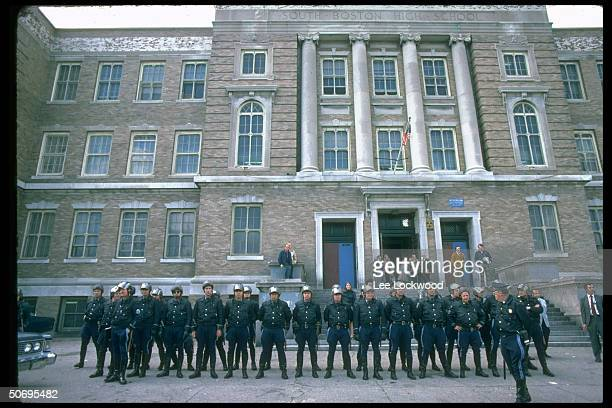 Boston police standing in line in front of South Boston High School during busing integration crisis