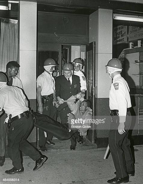 Boston Police wearing riot helmets and carrying batons drag an alleged looter from a store in Roxbury on June 1, 1967.