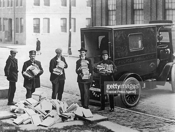 Boston police with a haul of 'subversive' literature confiscated during the postwar red scare which they are preparing to load into a police ambulance