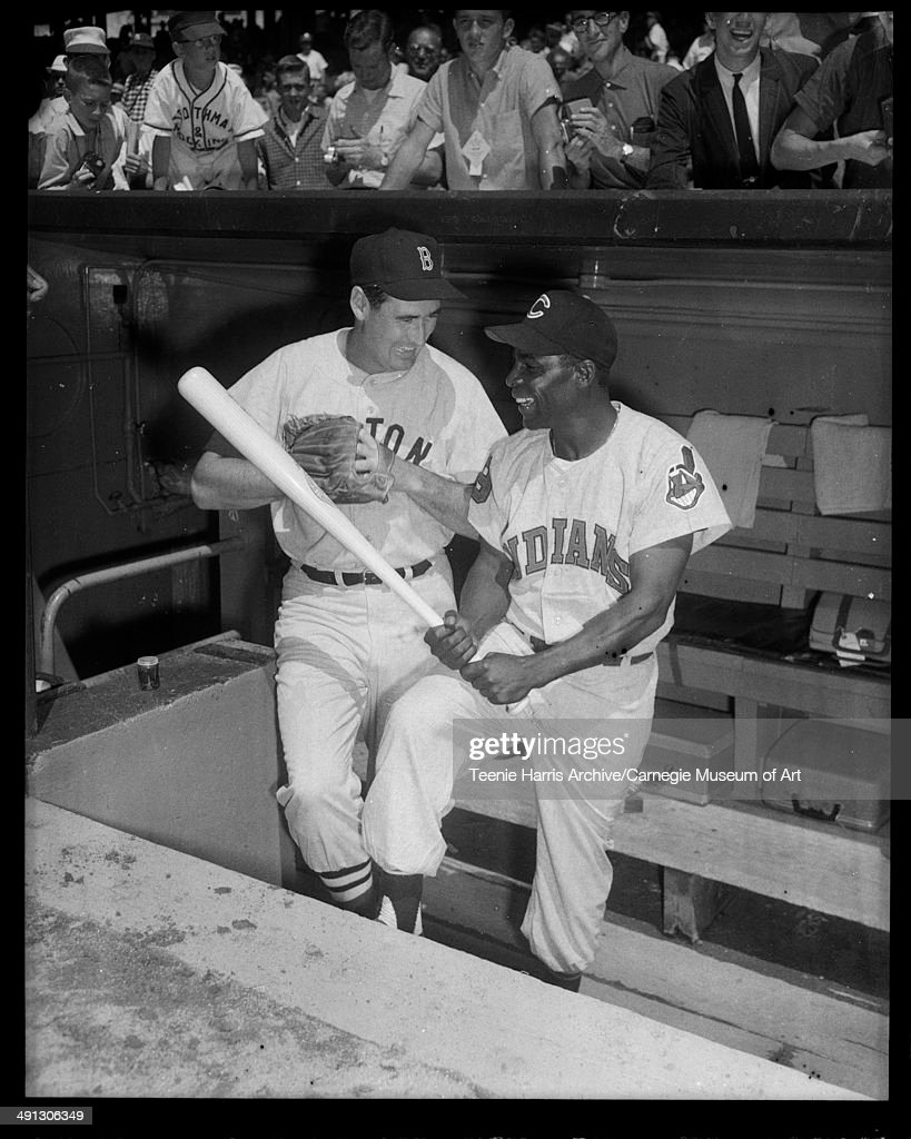 Boston Red So, baseball player Ted Williams and Cleveland Indians player Minnie Minoso, posed in dugout for 1959 All Star Game, Forbes Field, Pittsburgh, Pennsylvania, July 1959.