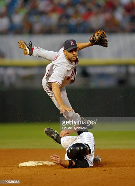 Boston Red Sox 2nd Baseman Alex Cora leaps over base runner Joe Crede and turns a double play during the game against the Chicago White Sox July 23...