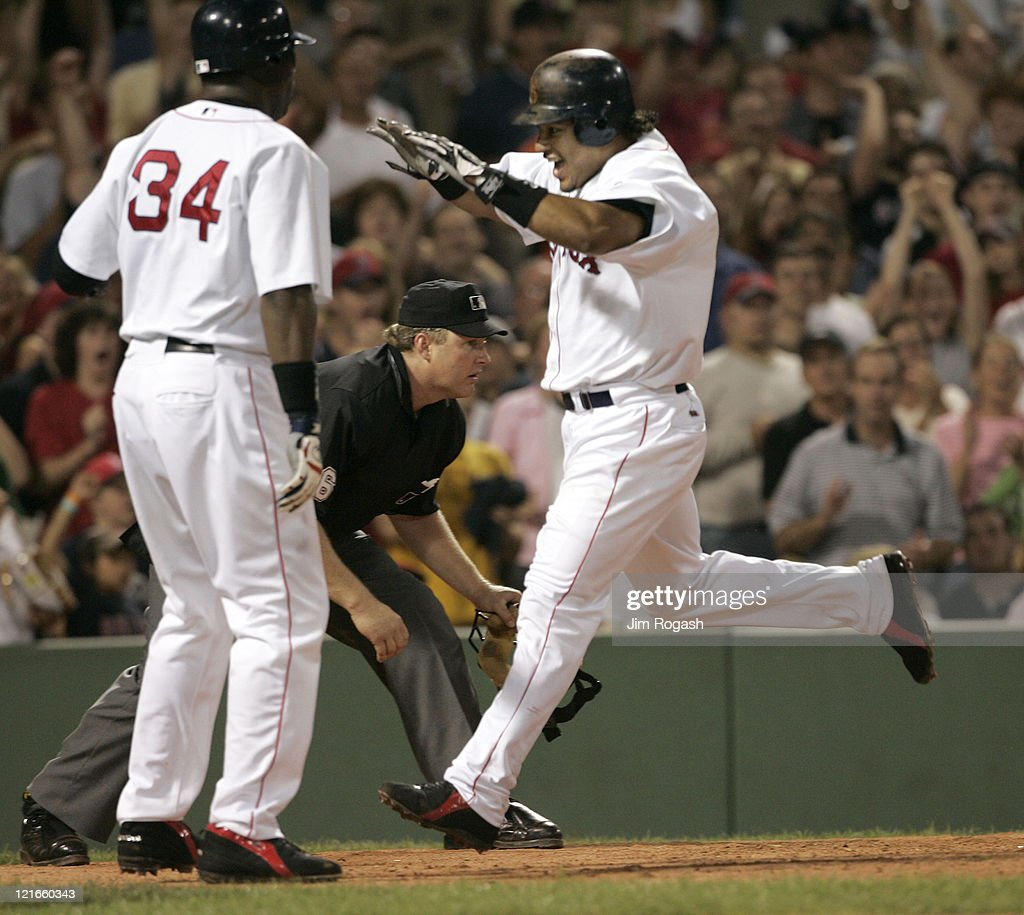 Boston Red Sox base runner Manny Ramirez, right, reacts as he scores a run against the Oakland Athletics at Fenway Park in Boston, July 8, 2004. The Red Sox won 8-7 in extra innings.